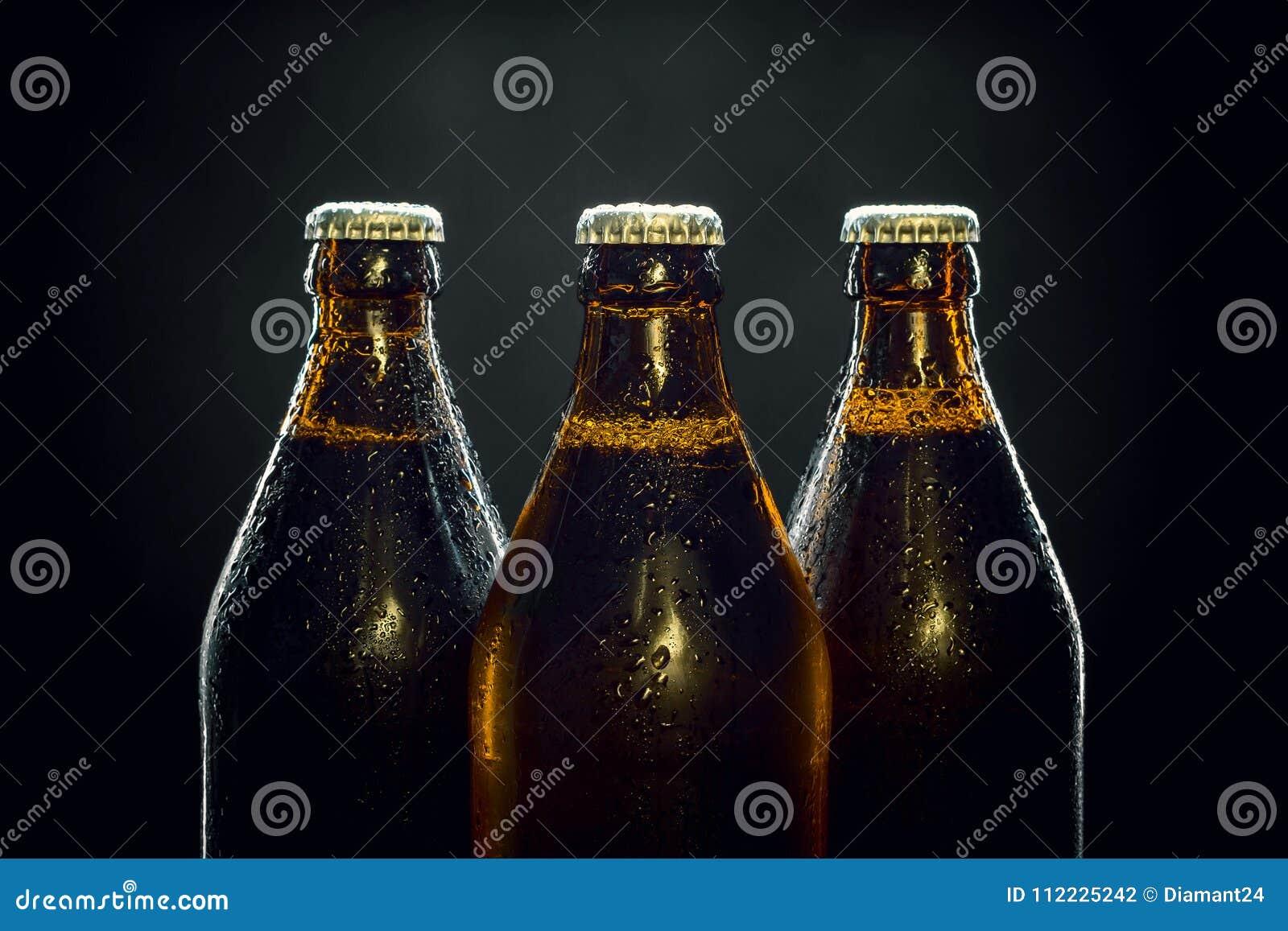 Tre kalla ölflaskor på svart