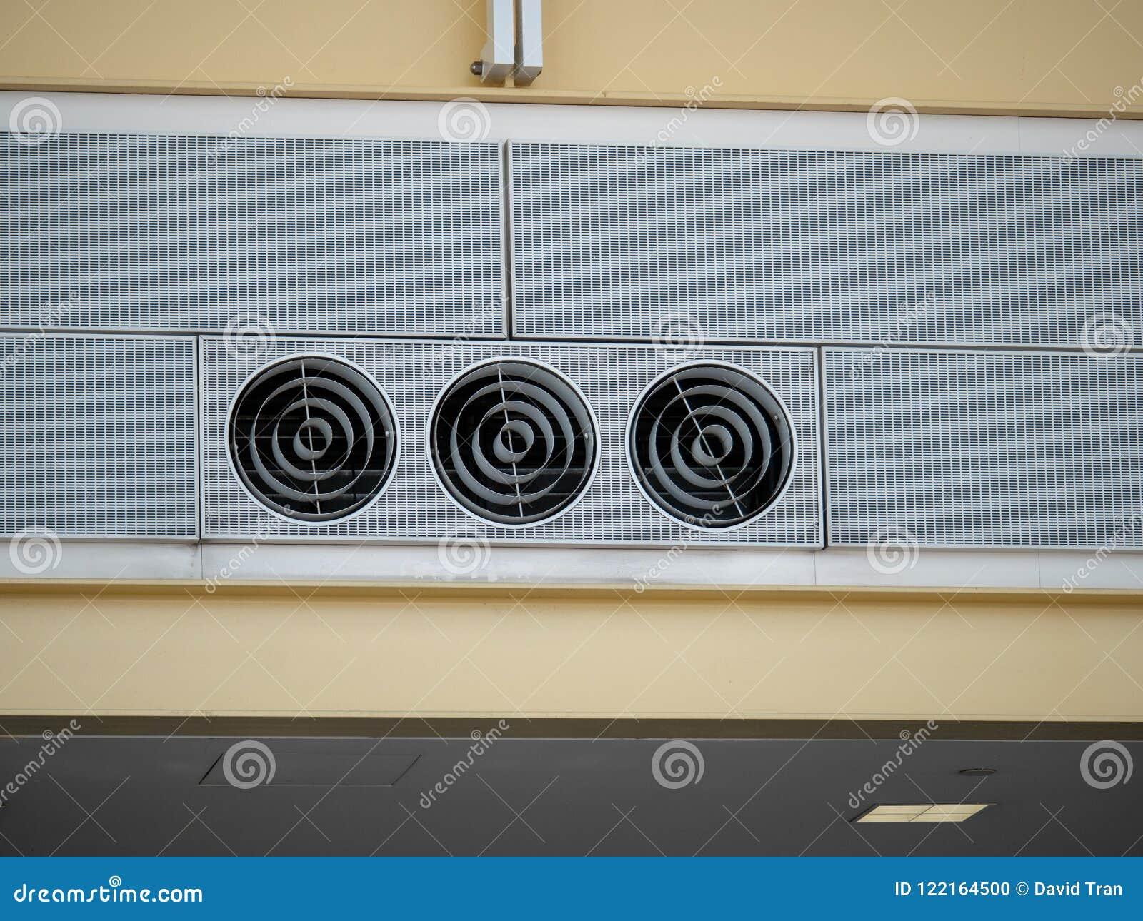 Tre kalla industriella fans för ventilationskanal sitter högt i en flygplatsinställning