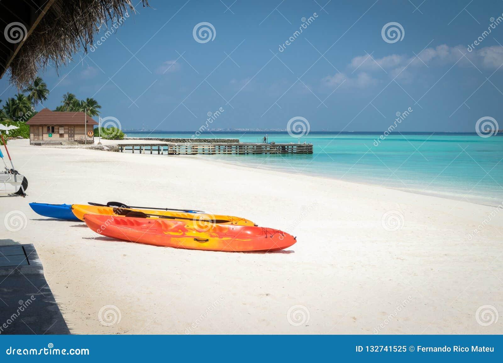 Tre kanoter på den vita sandstranden, stenar pir på turkoslagun i Maldiverna
