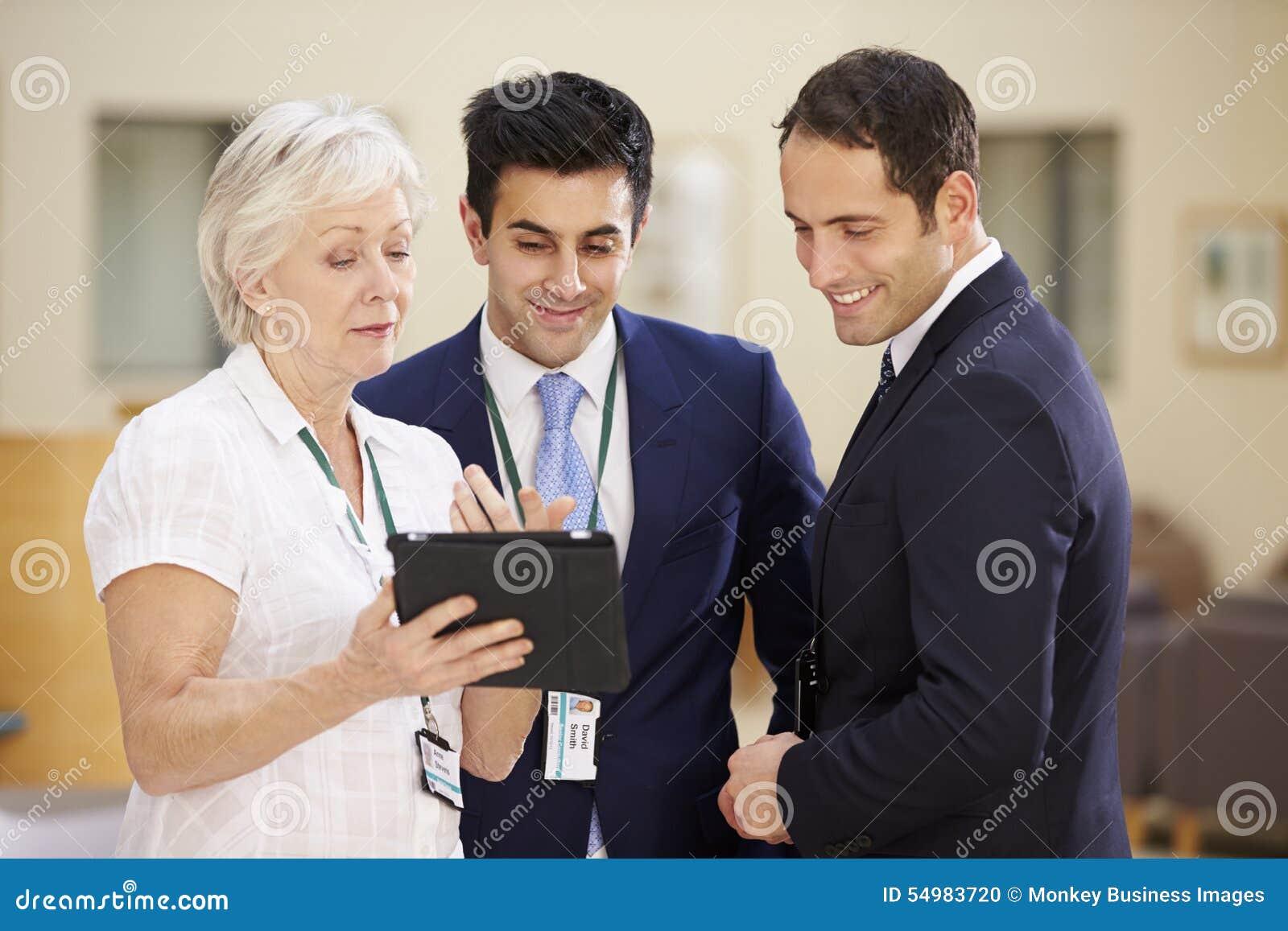 Tre konsulenter som diskuterar patientanmärkningar i sjukhus