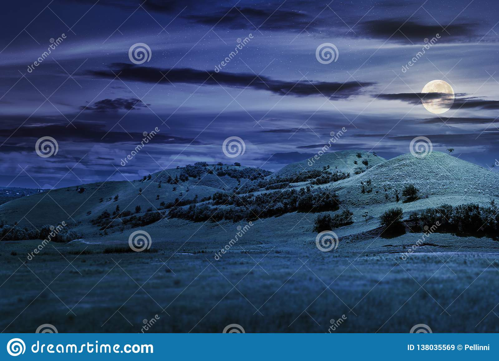 Tre kullar i sommarlandskap på natten
