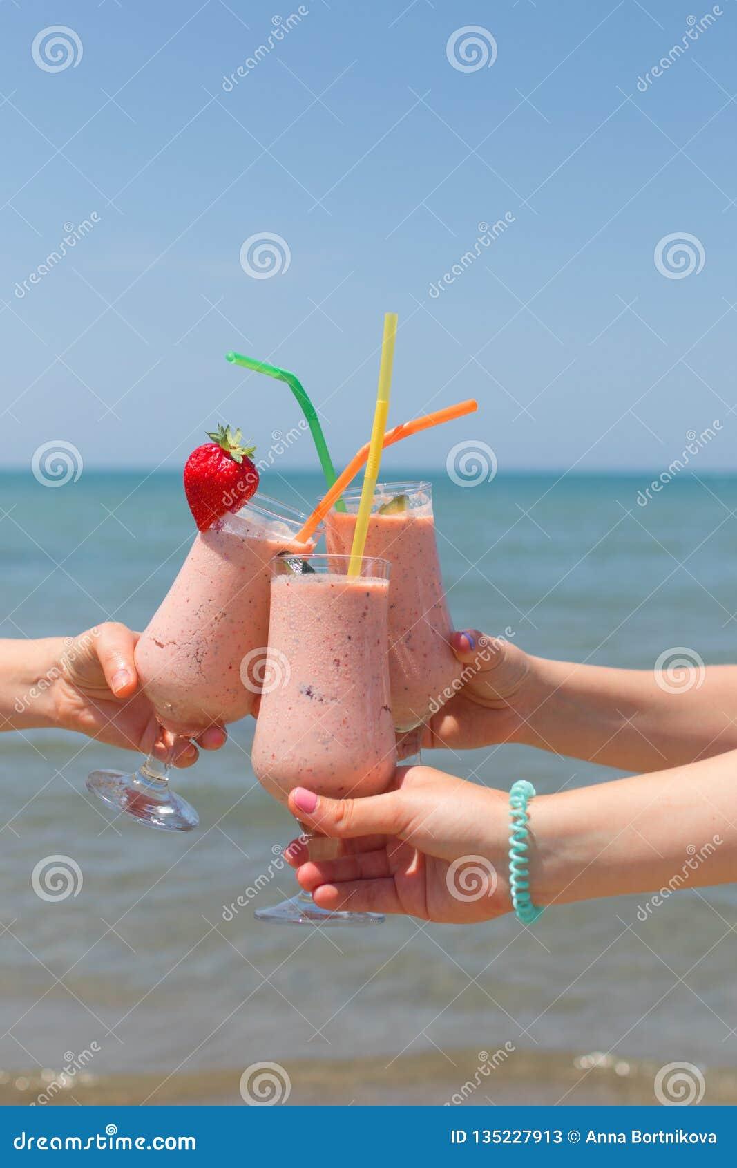 Tre kvinnliga händer rymmer jordgubbemilkshakar på bakgrunden av havet