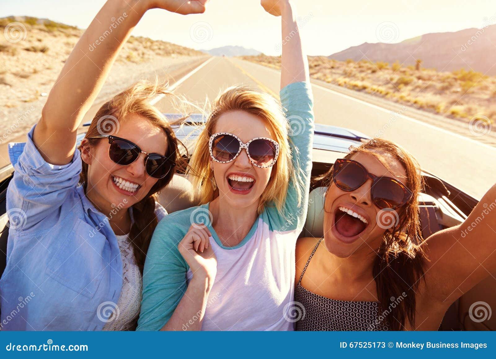 Tre kvinnliga vänner på vägtur i baksida av den konvertibla bilen