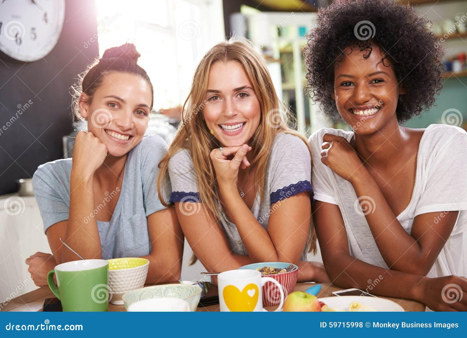 Tre kvinnliga vänner som hemma tycker om frukosten tillsammans