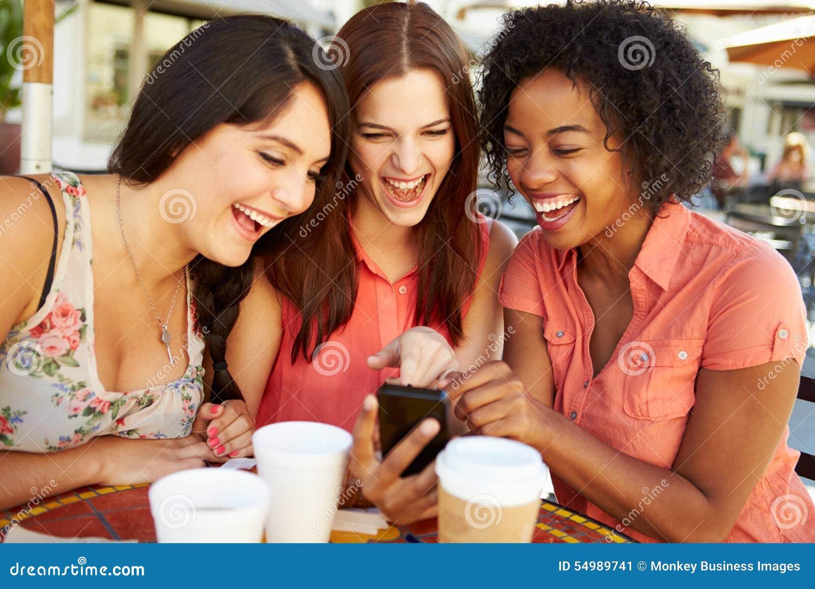 Tre kvinnliga vänner som läser textmeddelandet i CafÅ ½