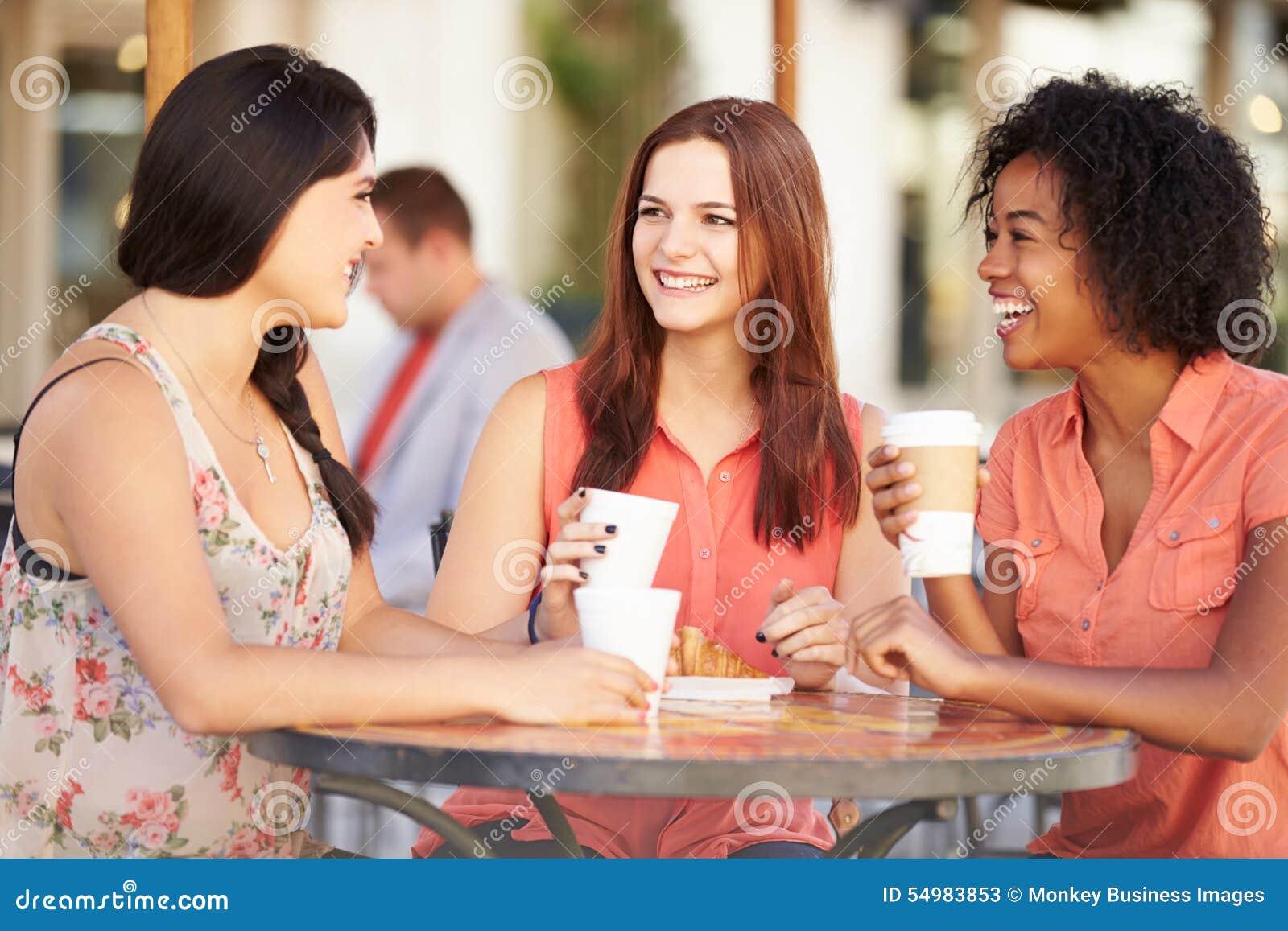 Tre kvinnliga vänner som möter i CafÅ ½