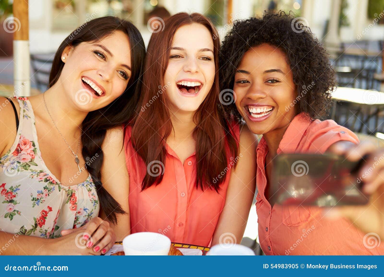 Tre kvinnliga vänner som tar Selfie i CafÅ ½