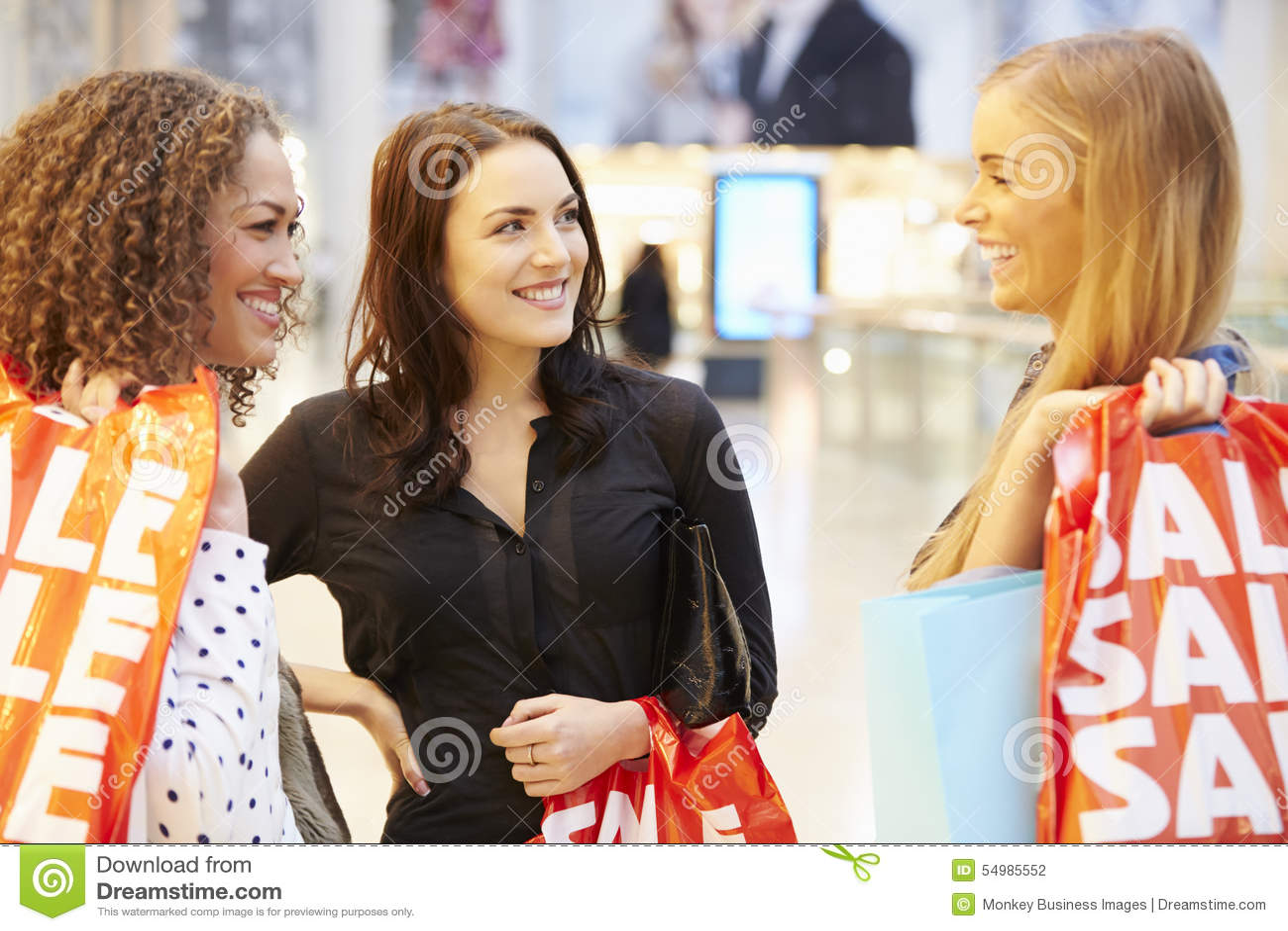 Tre kvinnliga vänner som tillsammans shoppar i galleria