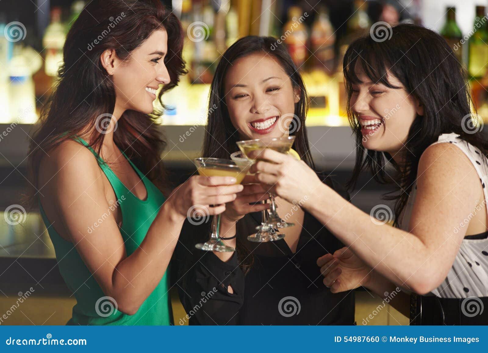 Tre kvinnliga vänner som tycker om drinken i coctailstång