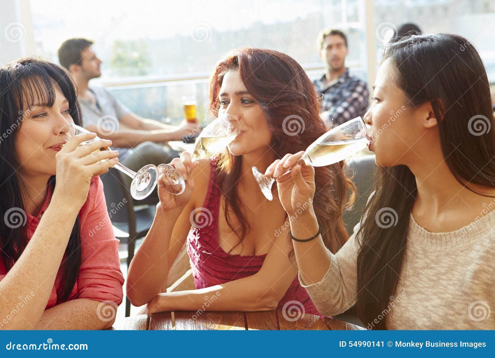 Tre kvinnliga vänner som tycker om drinken på den utomhus- takstången