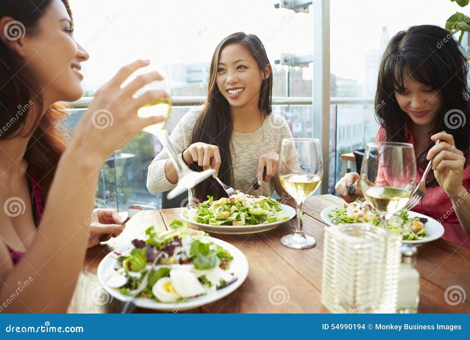 Tre kvinnliga vänner som tycker om lunch på takrestaurangen
