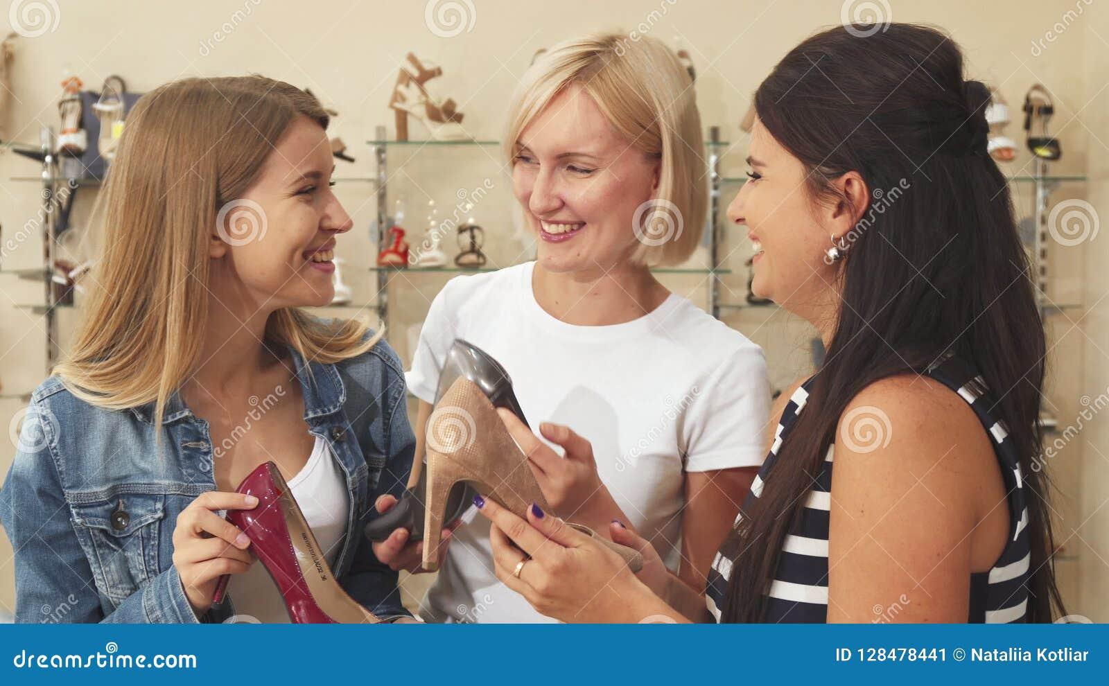 Tre kvinnor som diskuterar skor i sko, shoppar