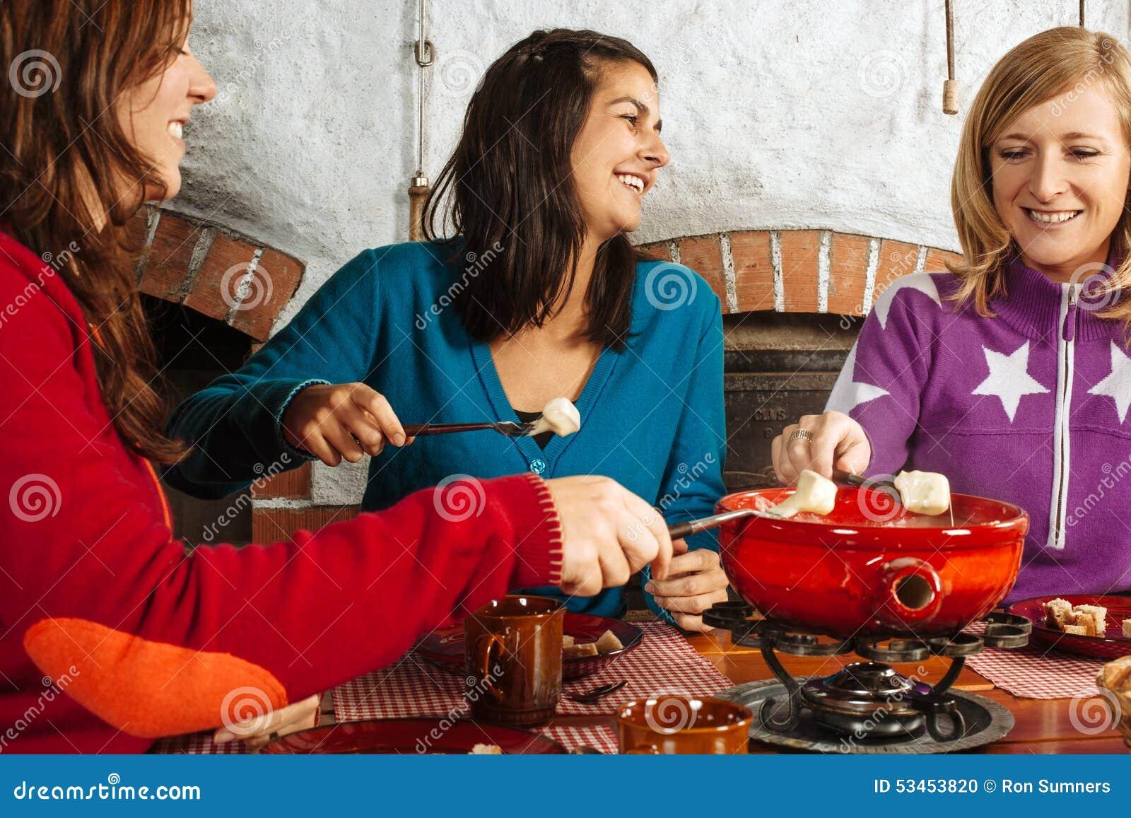 Tre kvinnor som har fonduematställen
