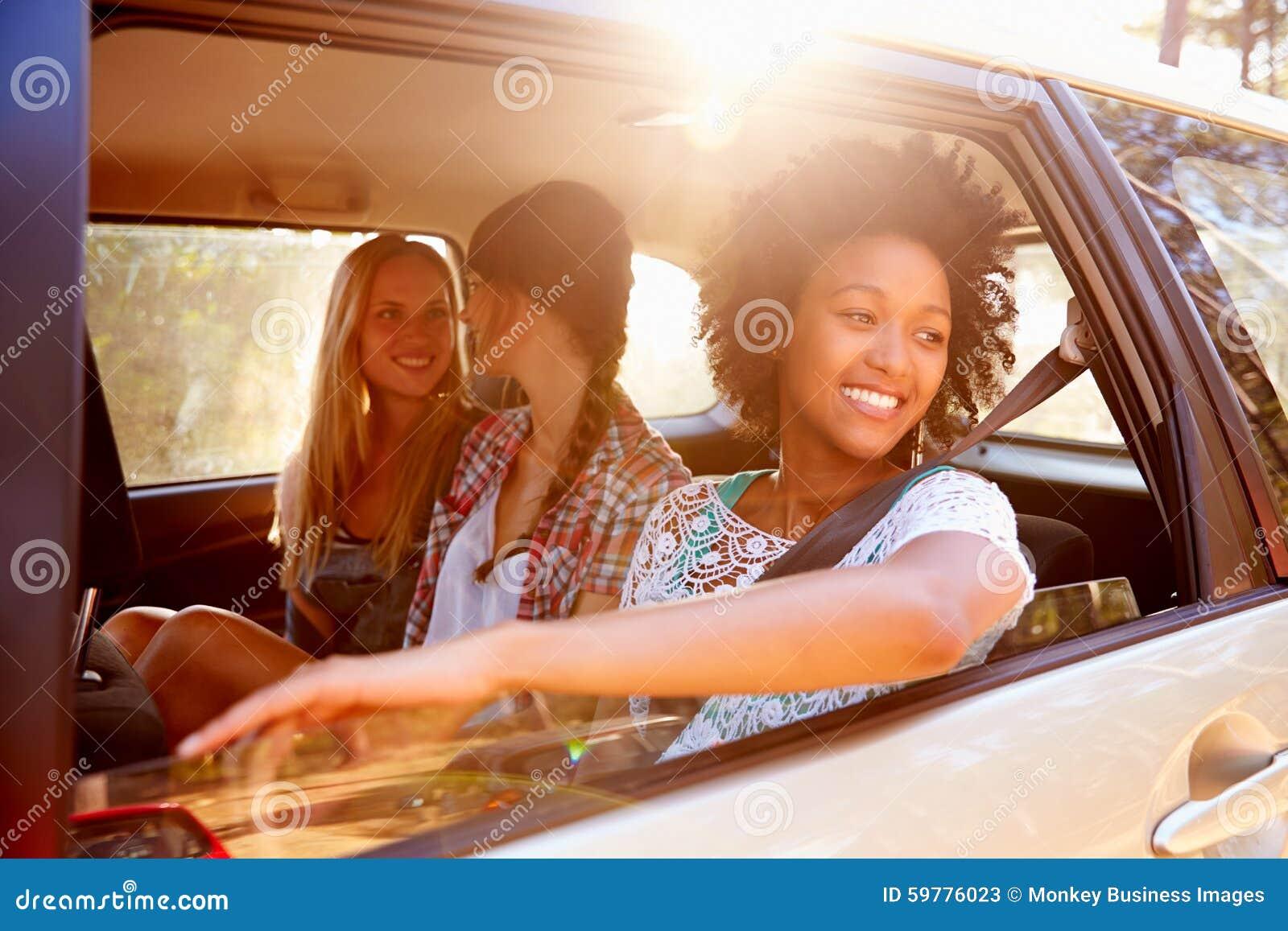 Tre kvinnor som sitter i bakre Seat av bilen på vägtur
