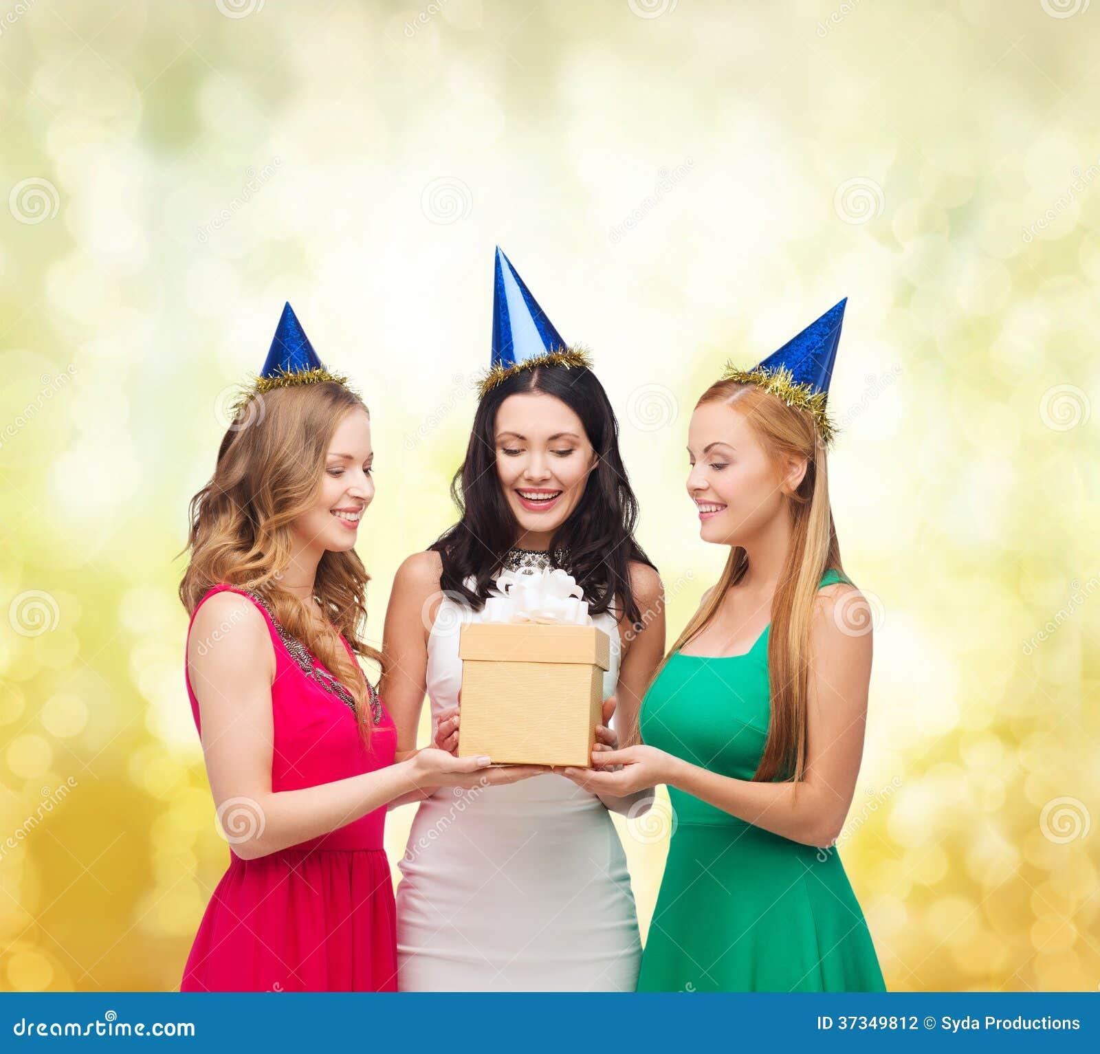 Tre le kvinnor i blåa hattar med gåvaasken