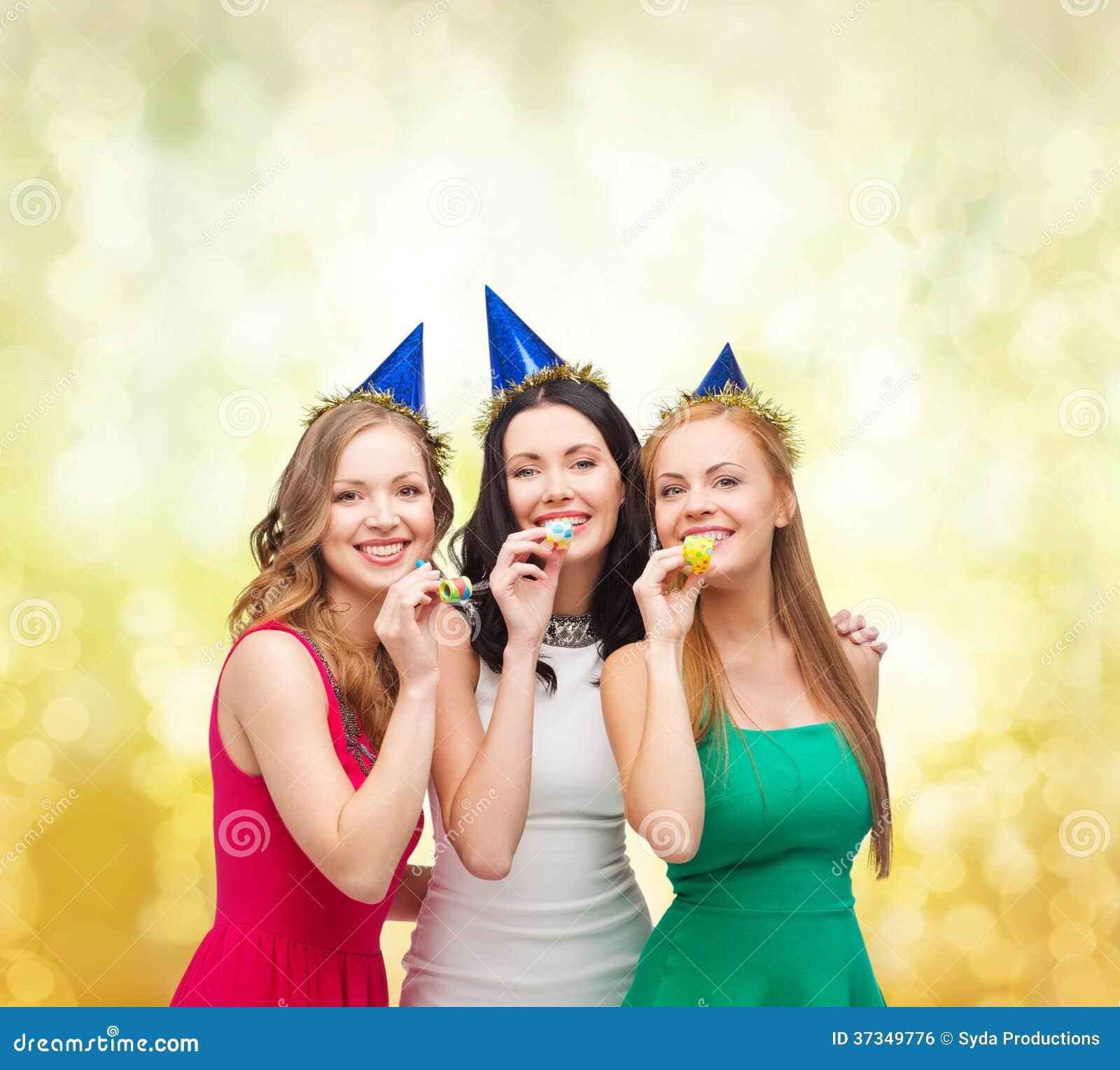 Tre le kvinnor i hattar som blåser favörhorn