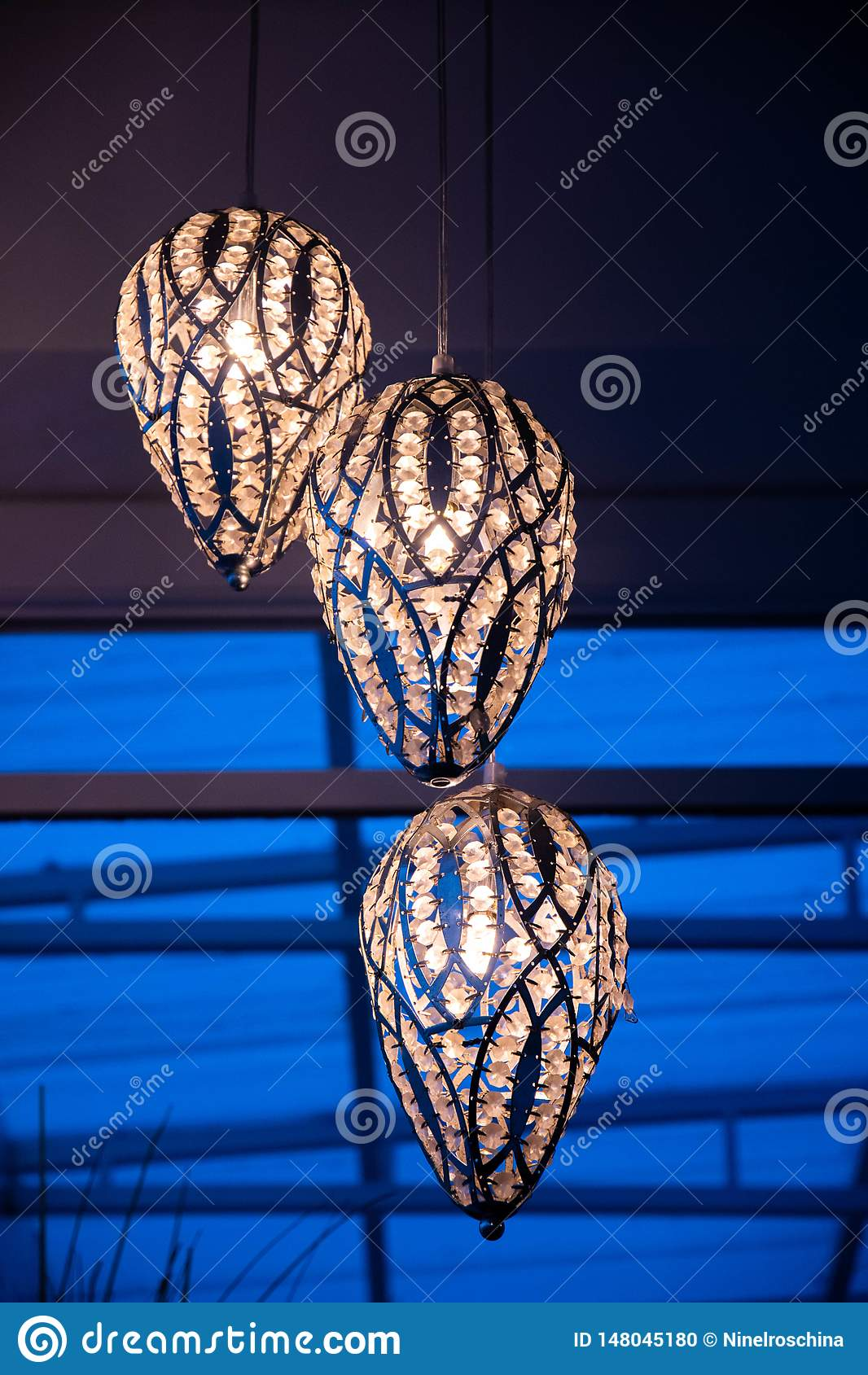 Tre liknande utsmyckat försilvrar lampor med skinande kristaller i mörker Modern ljuskronacloseup