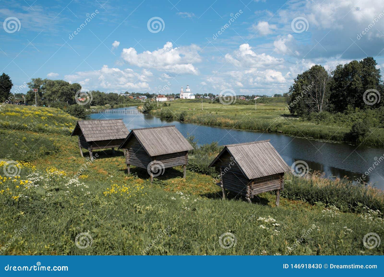 Tre lilla gamla trähus på höga styltor vid floden