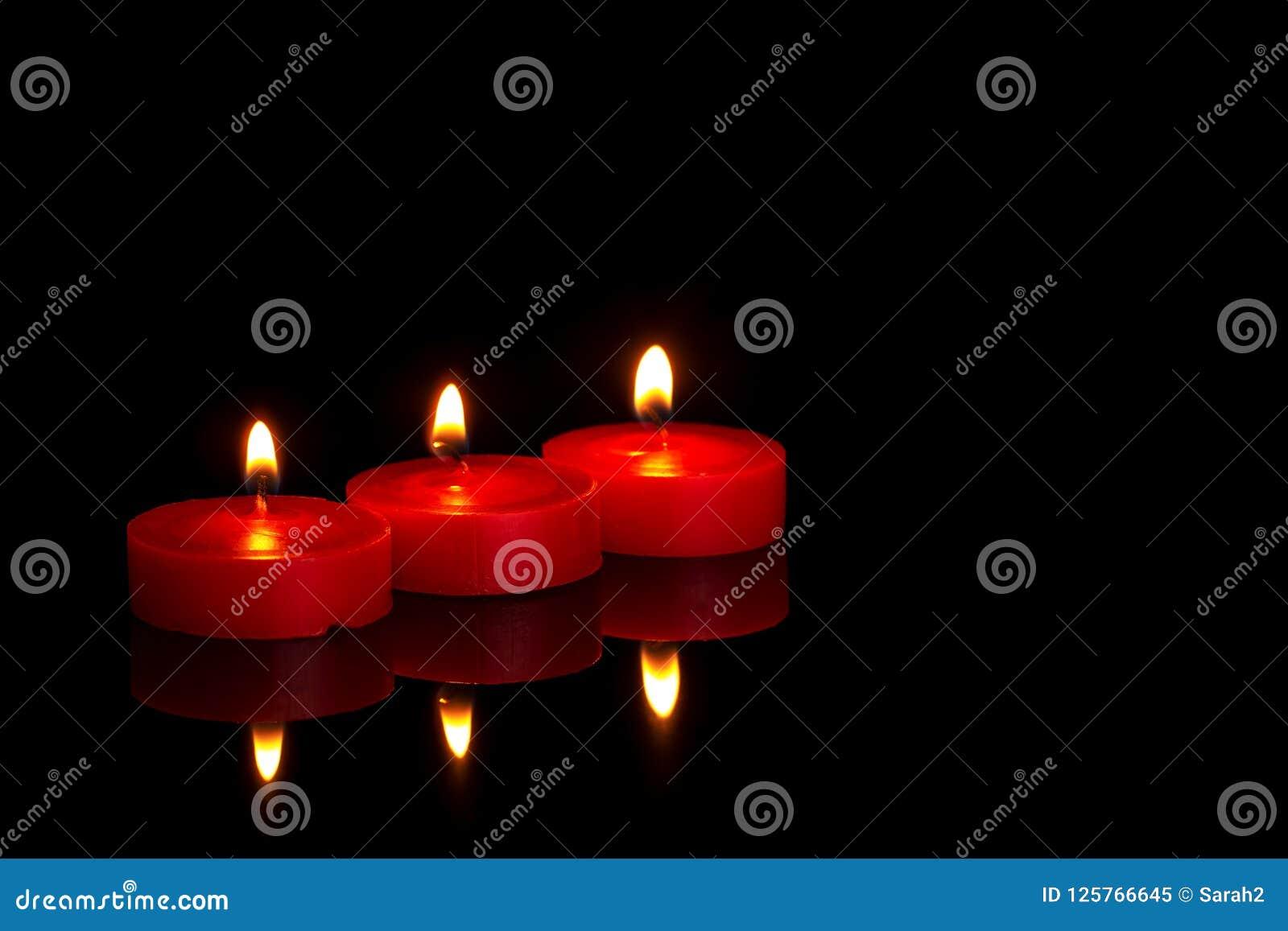 Tre lilla röda stearinljus, tealights som bränner på natten på svart In memoriam eller klosterbroder kanske