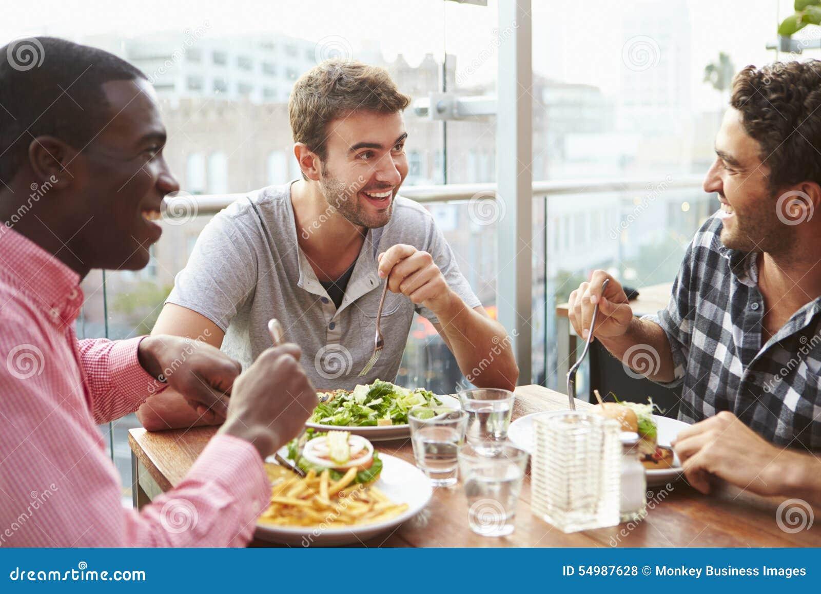 Tre manliga vänner som tycker om lunch på takrestaurangen
