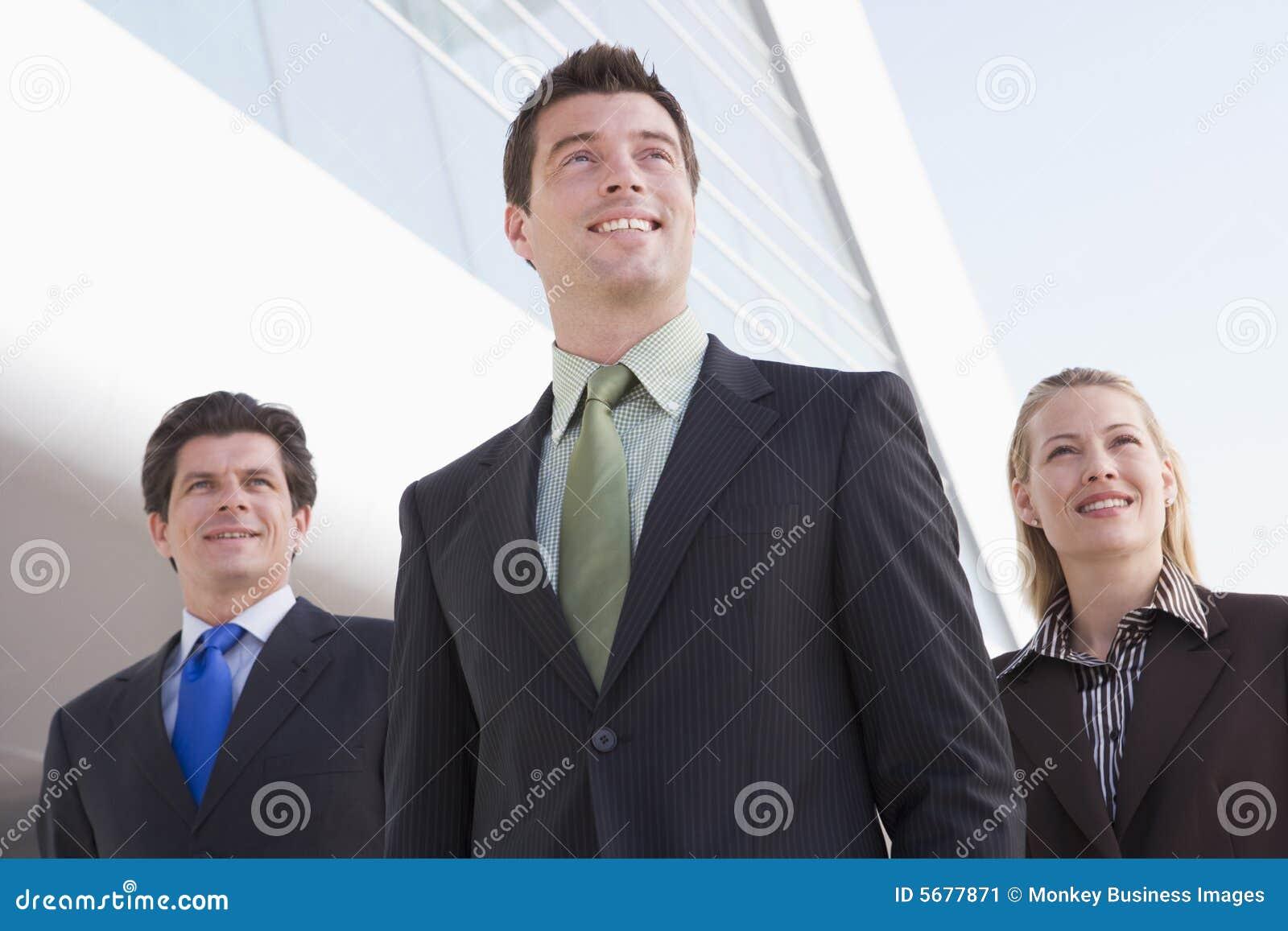 Tre persone di affari che si levano in piedi all aperto dalla costruzione