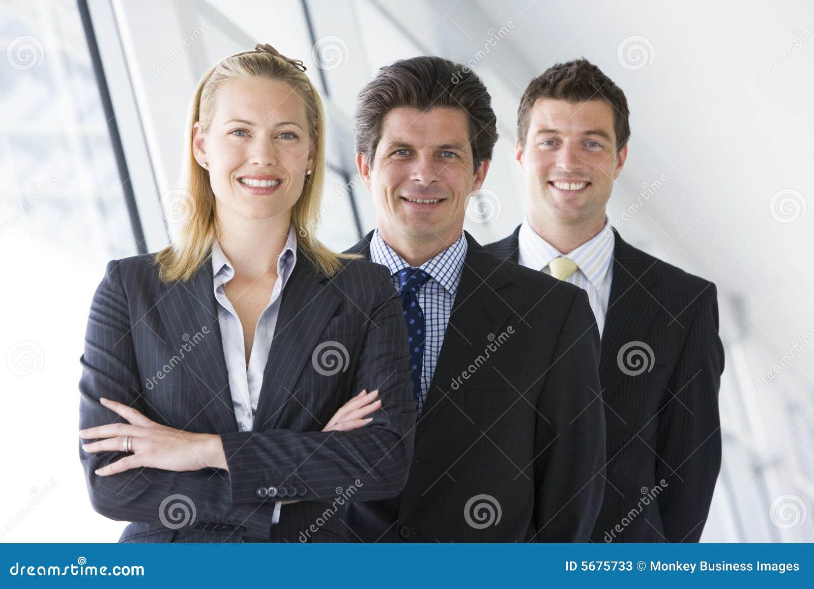 Tre persone di affari che si levano in piedi nel sorridere del corridoio