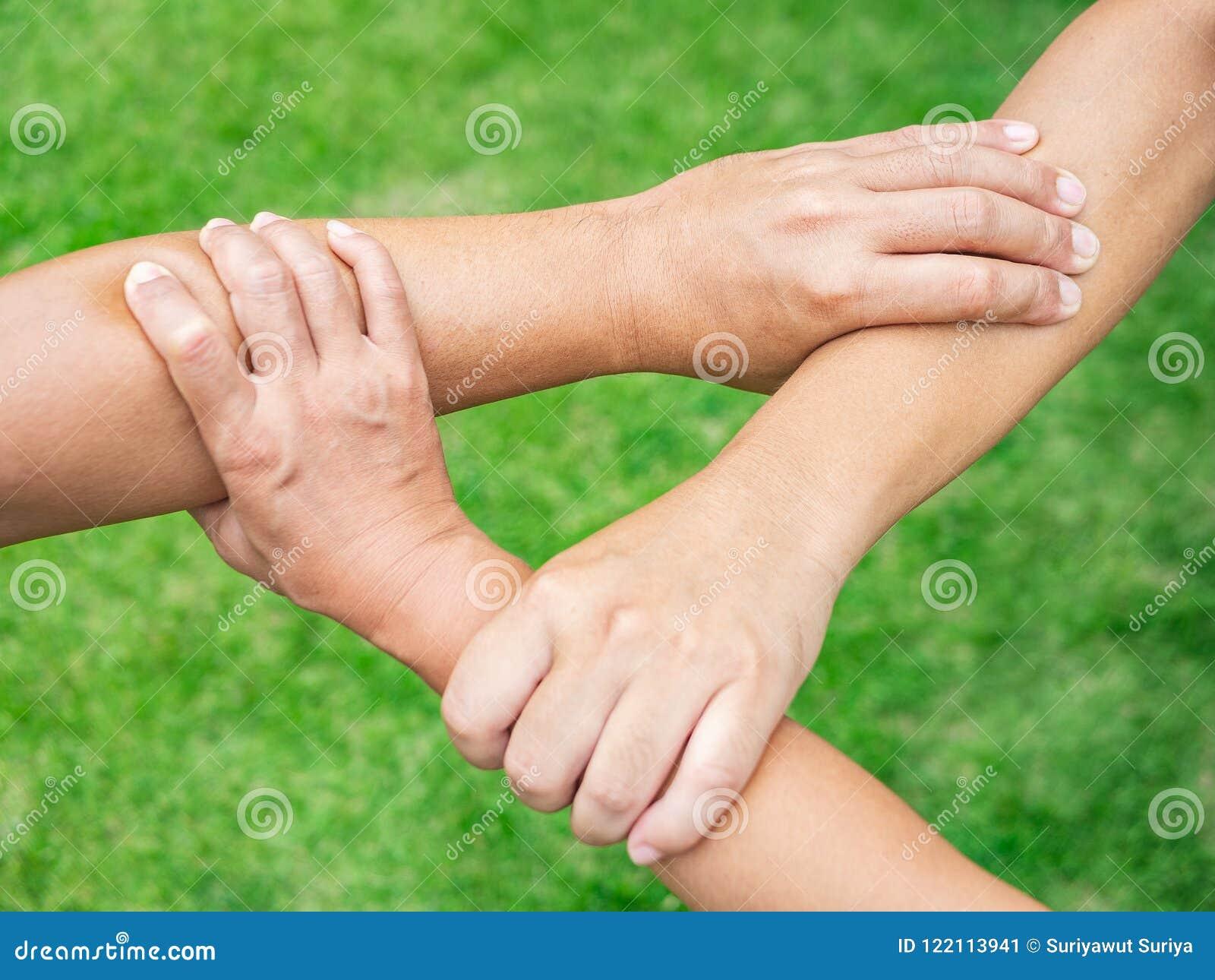 Tre personer sammanfogar händer tillsammans på gräsbakgrund kamratskap