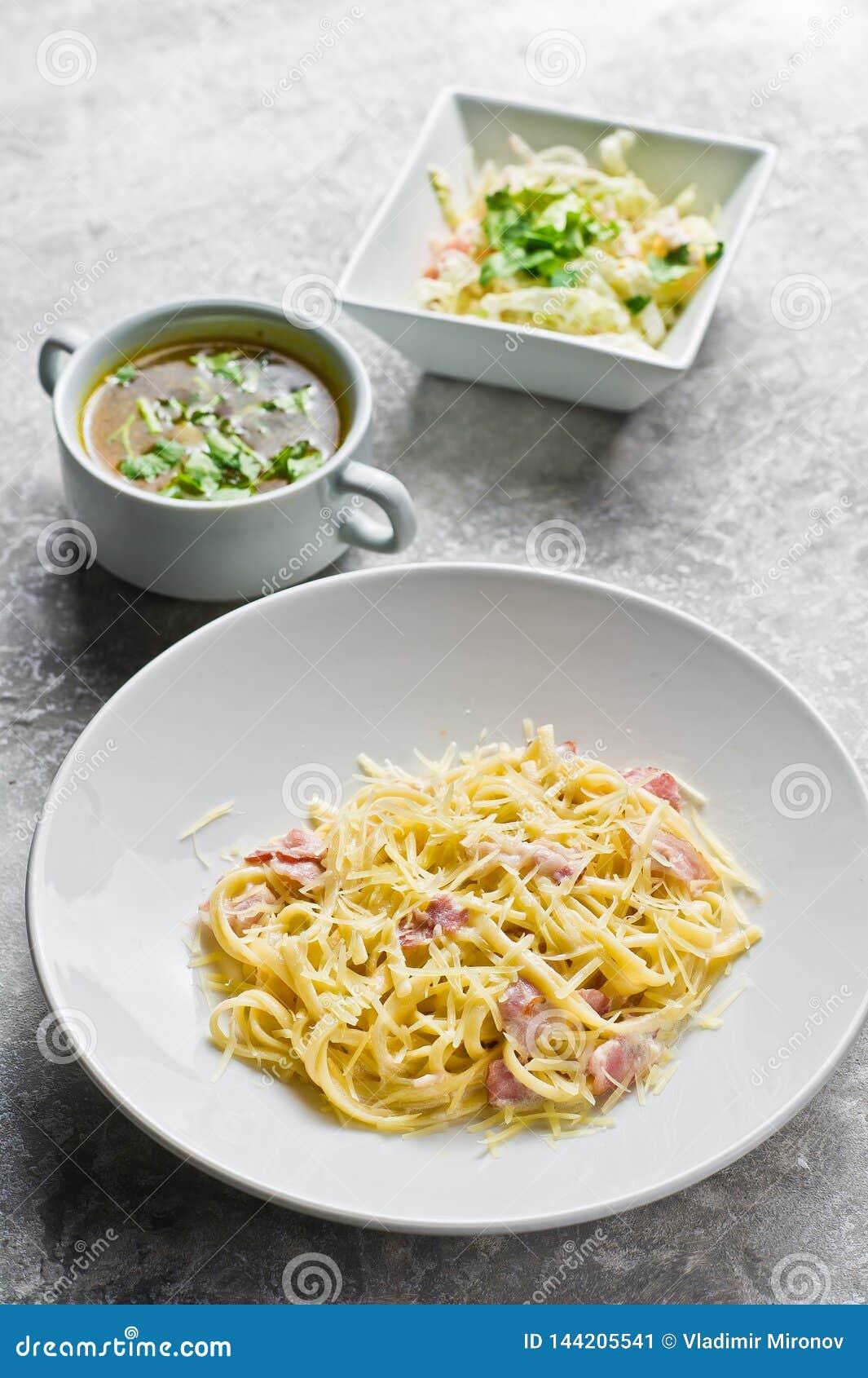 Tre piatti nel ristorante, nella pasta Carbonara, nell insalata verde e nella minestra di pollo