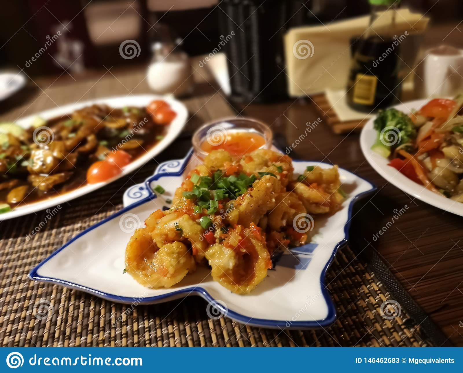 Tre piatti orientali con le tagliatelle del manzo, dei gamberetti, dei pomodori, delle carote, del peperone e di riso