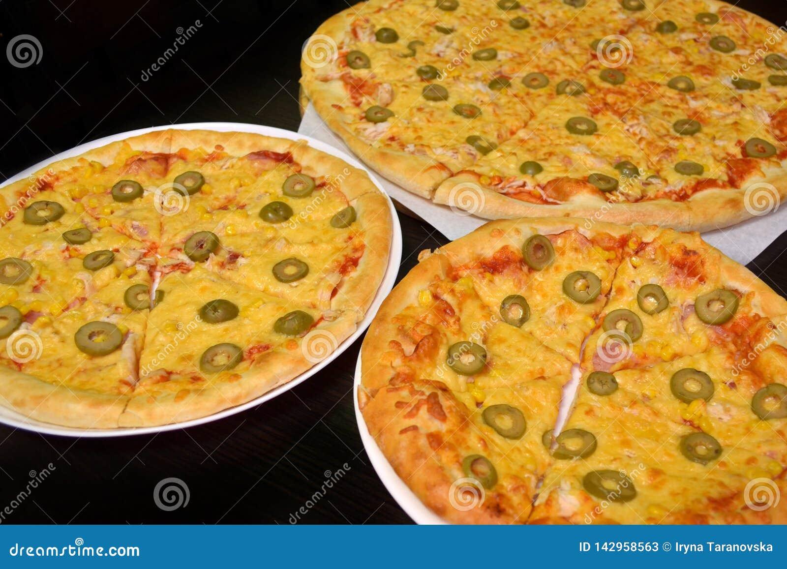 Tre pizze con formaggio ed olive delle dimensioni differenti su un fondo scuro