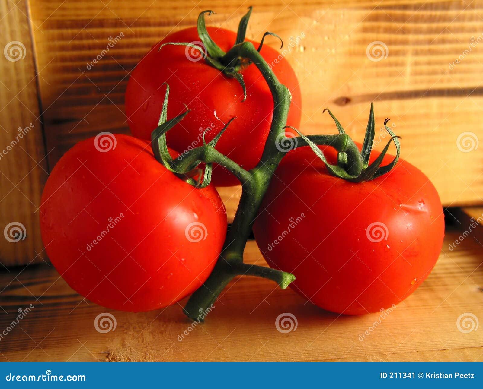 Tre pomodori rossi su legno
