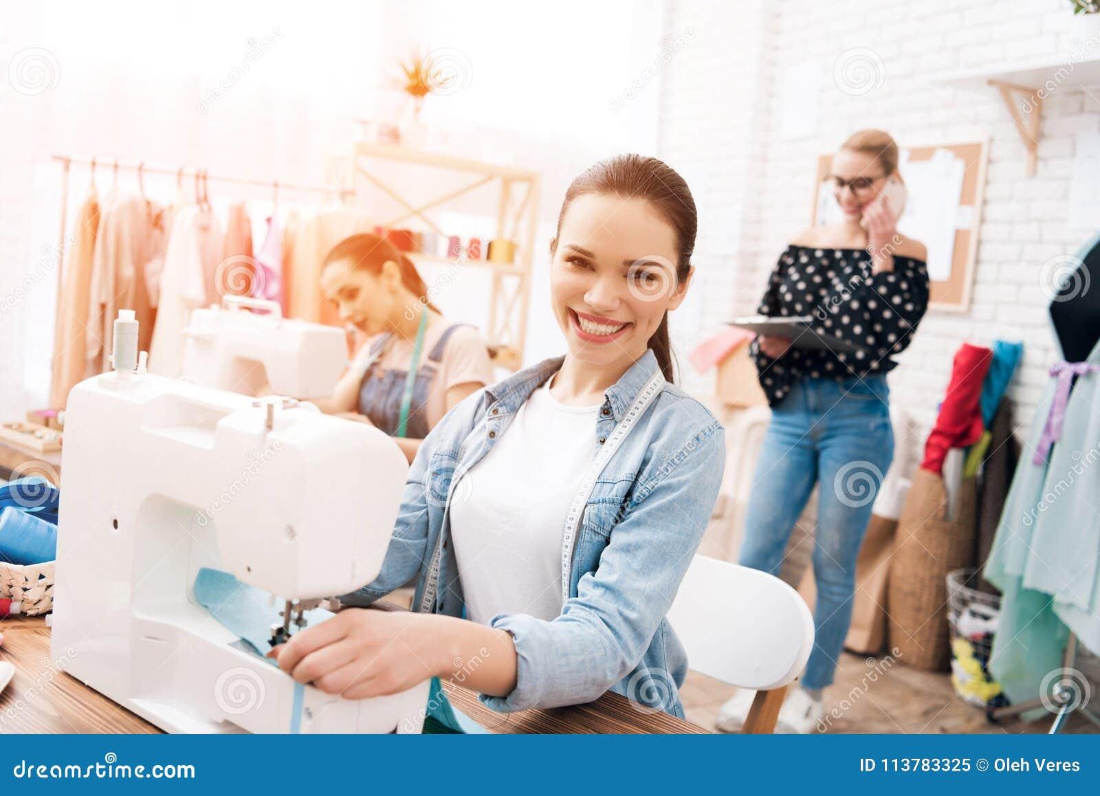 Tre ragazze alla fabbrica dell indumento Stanno sedendo dietro le macchine per cucire