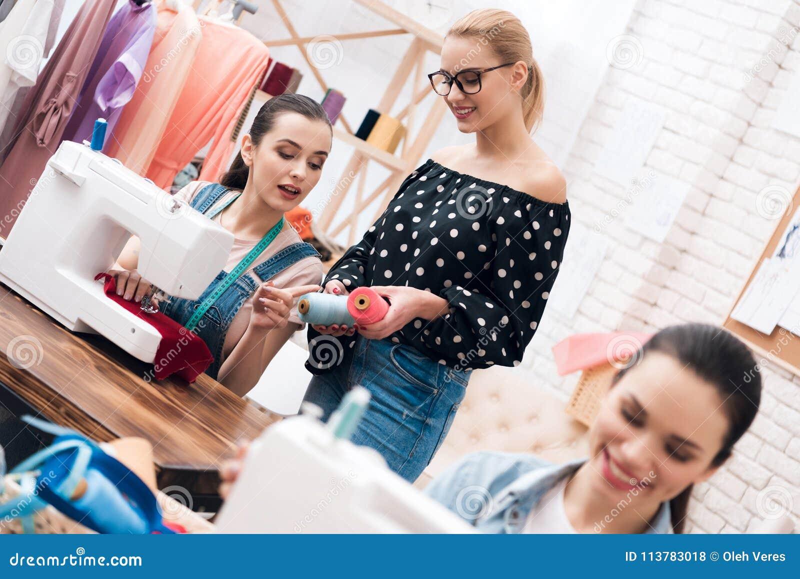Tre ragazze alla fabbrica dell indumento Stanno sedendo dietro le macchine per cucire e scegliere infila per il nuovo vestito