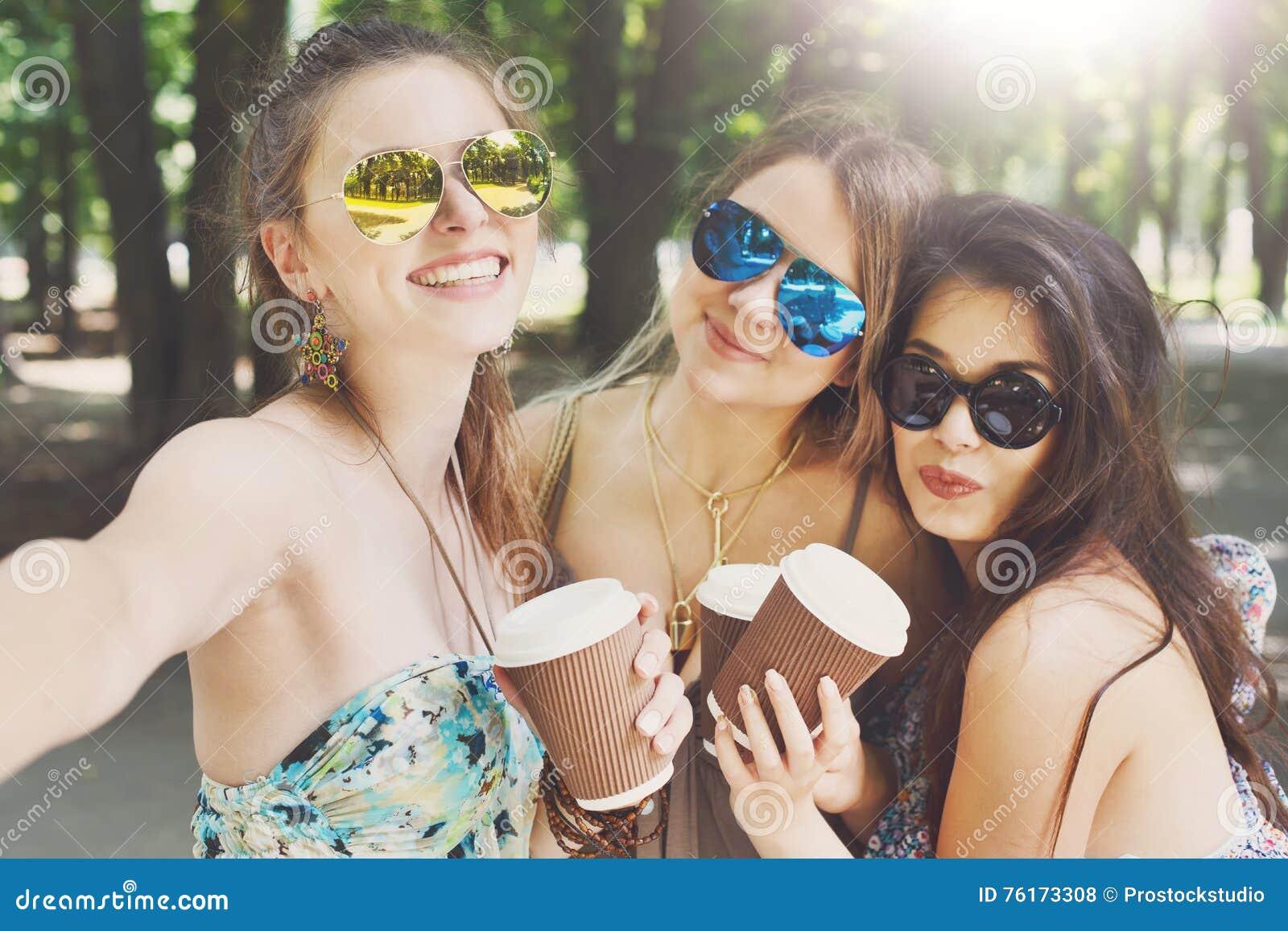 Tre ragazze alla moda eleganti di bello giovane boho che camminano nel parco