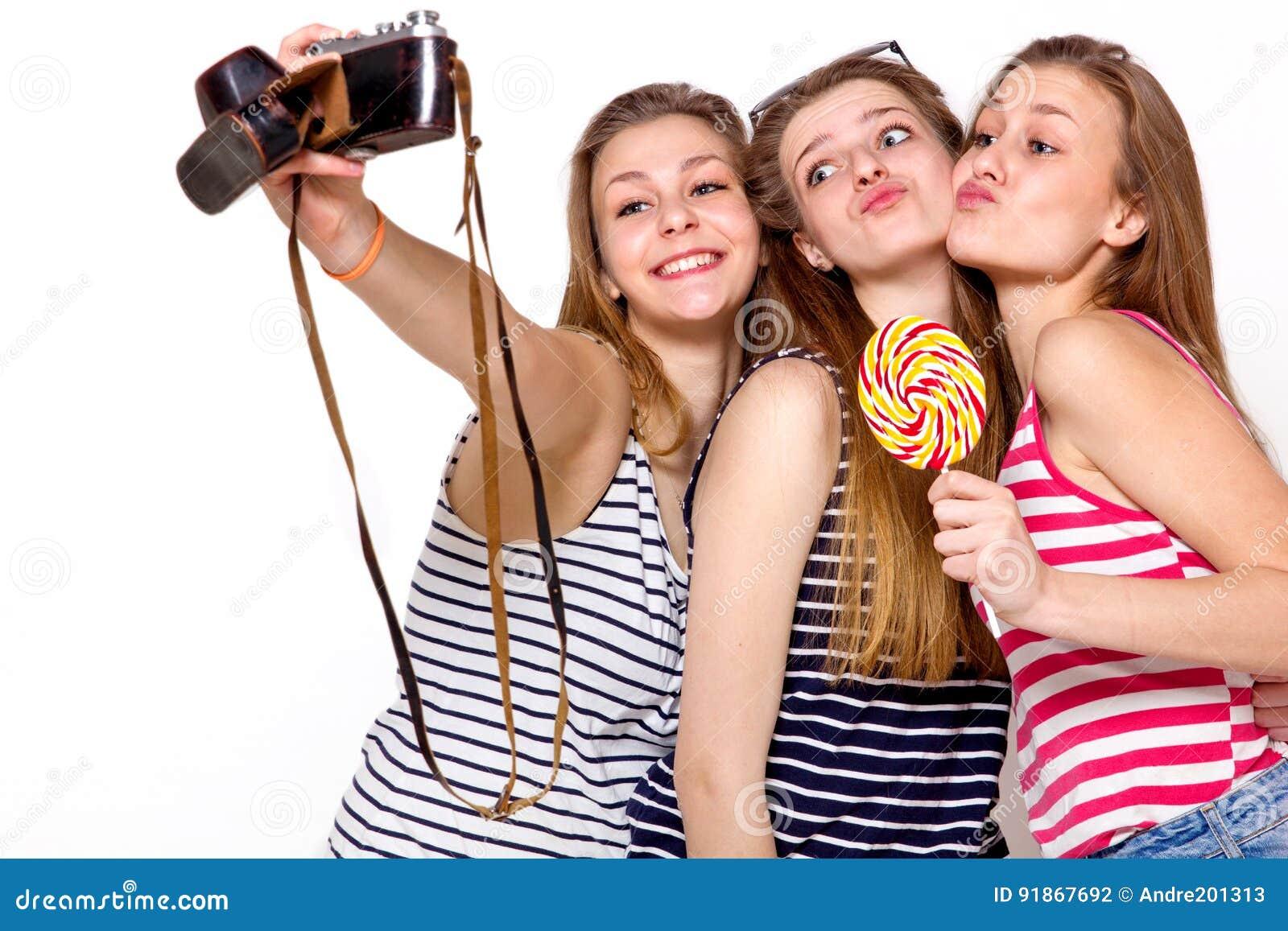 Tre ragazze stanno divertendo con la macchina fotografica