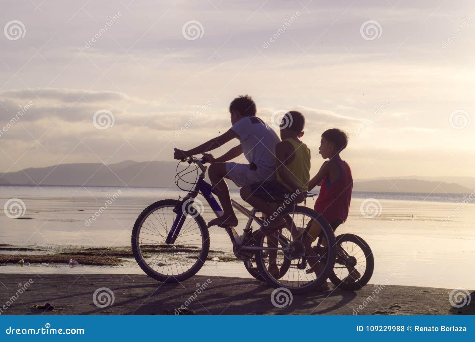 Tre Ragazzi Che Guidano Sulla Bicicletta Alla Riva Di Mare Siluette