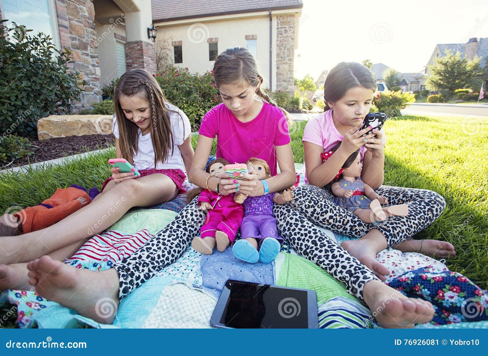 Tre små flickor som är tankfulla med deras smarta telefoner ee890b17e38d9