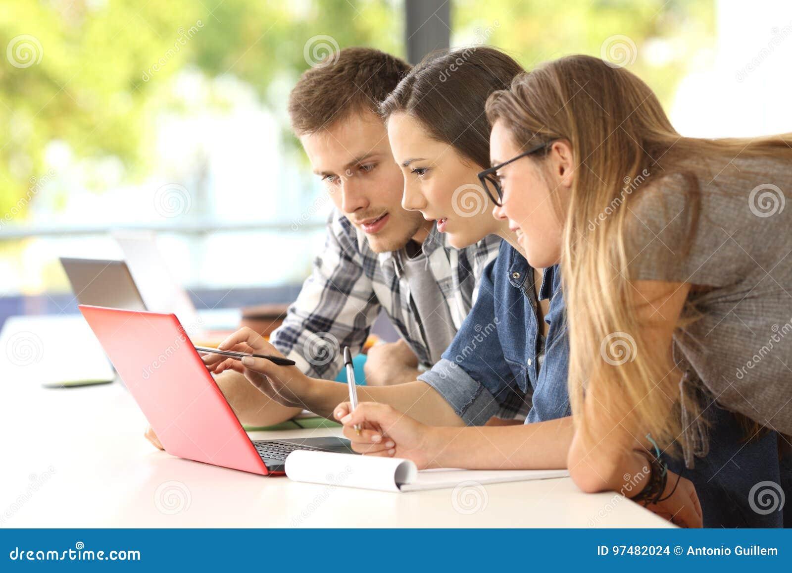 Tre studenti che studiano insieme sulla linea