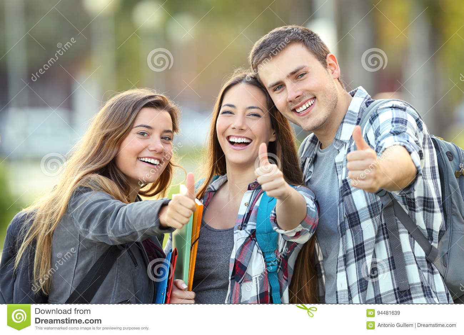 Tre studenti felici con i pollici su