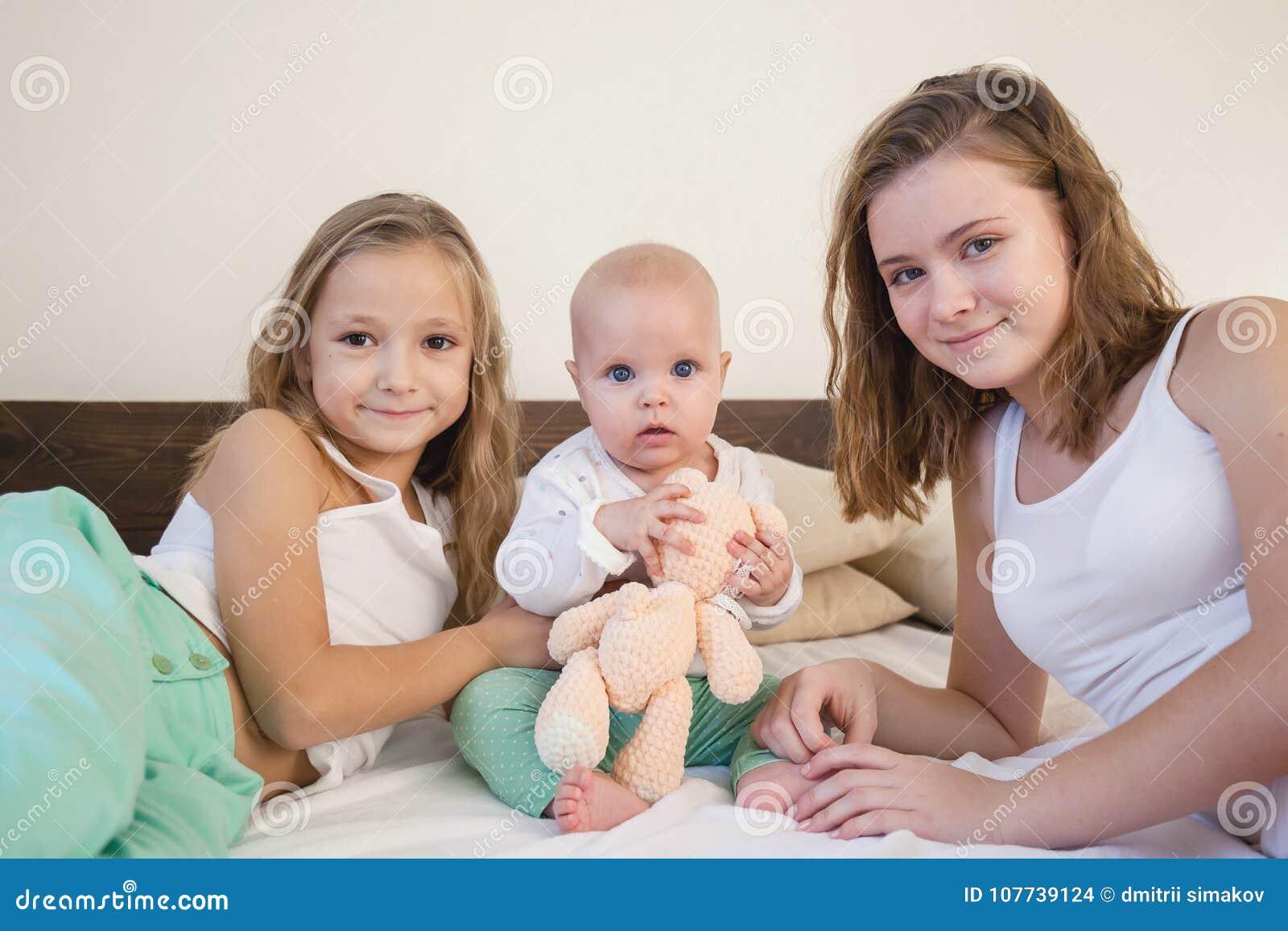 Tre systrar behandla som ett barn flickabarn i morgonen på sängen i sovrummet