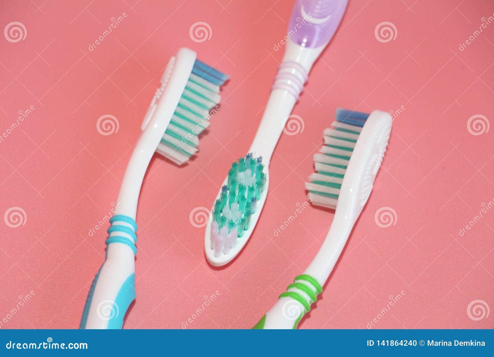 Tre tandborstar på en rosa bakgrund Muntlig hygien