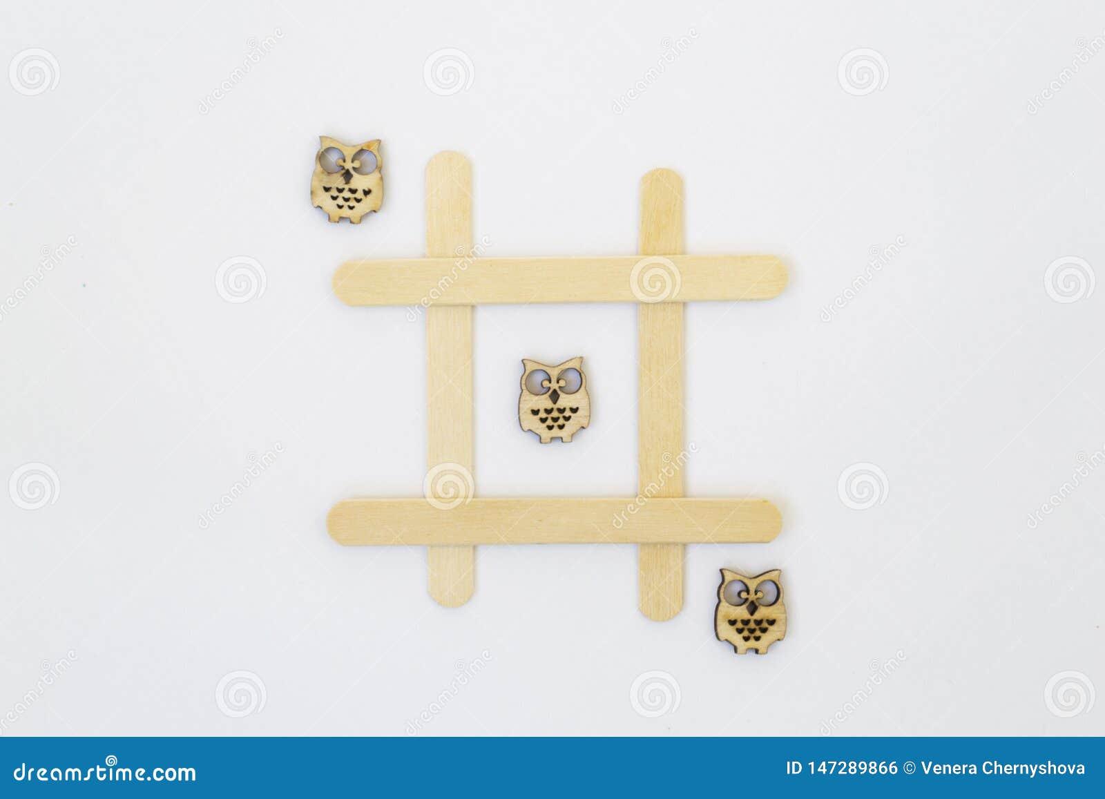 Tre träugglor ligger i rad i en linje i leken av muskelryckning-TAC-tån, i ett raster på en vit bakgrund