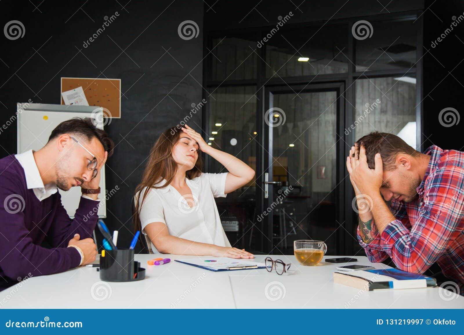 Tre unga affärsmän har huvudvärken på kontoret, ledset fel