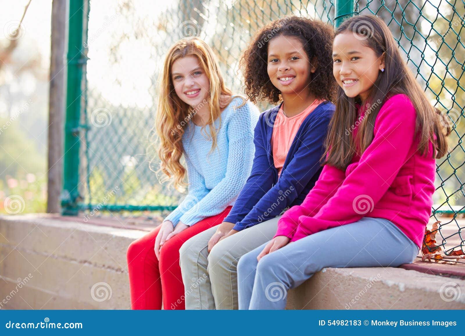 Tre unga flickor som ut hänger i, parkerar tillsammans