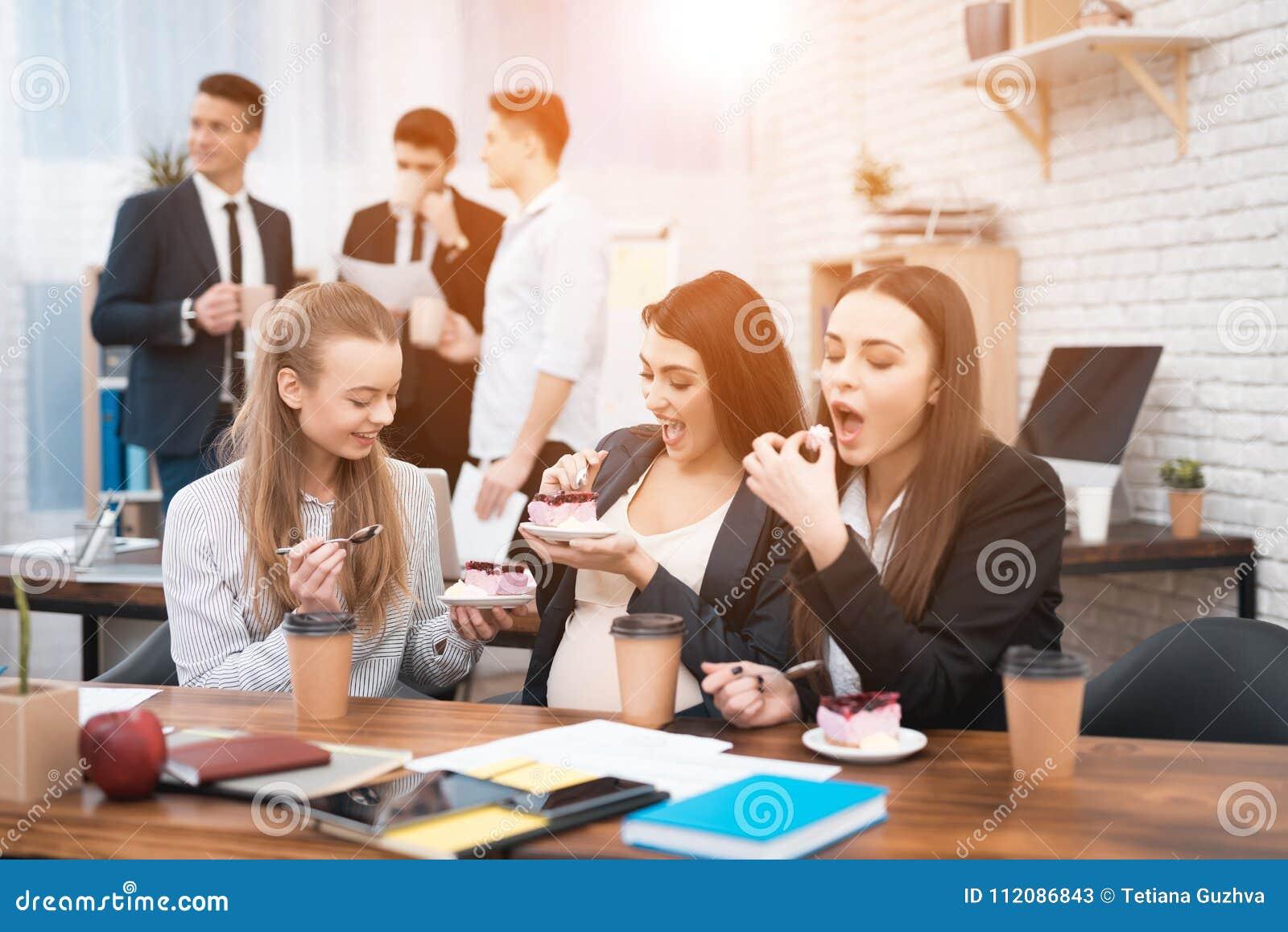 Tre unga gulliga flickor som i regeringsställning äter den söta kakan på lunchtime Äta lunch avbrottet