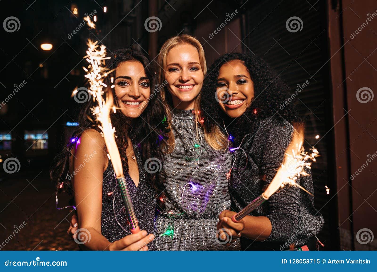 Tre unga kvinnliga vänner som tycker om helgdagsafton för nya år