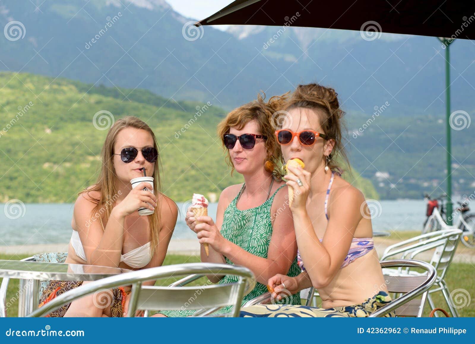 Tre unga kvinnor på stranden