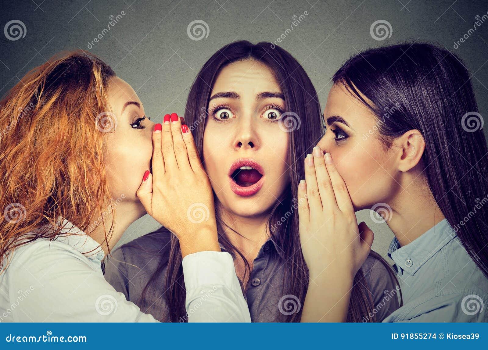 Tre unga kvinnor som berättar viska ett hemligt skvaller i örat