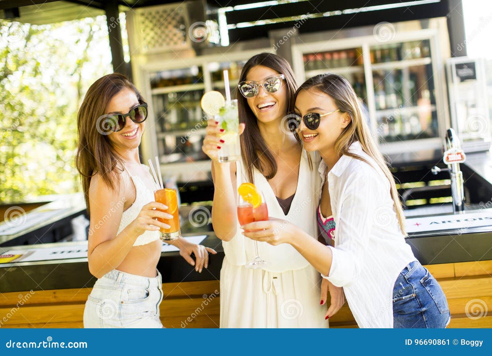 Tre unga kvinnor som dricker coctais i strandstång