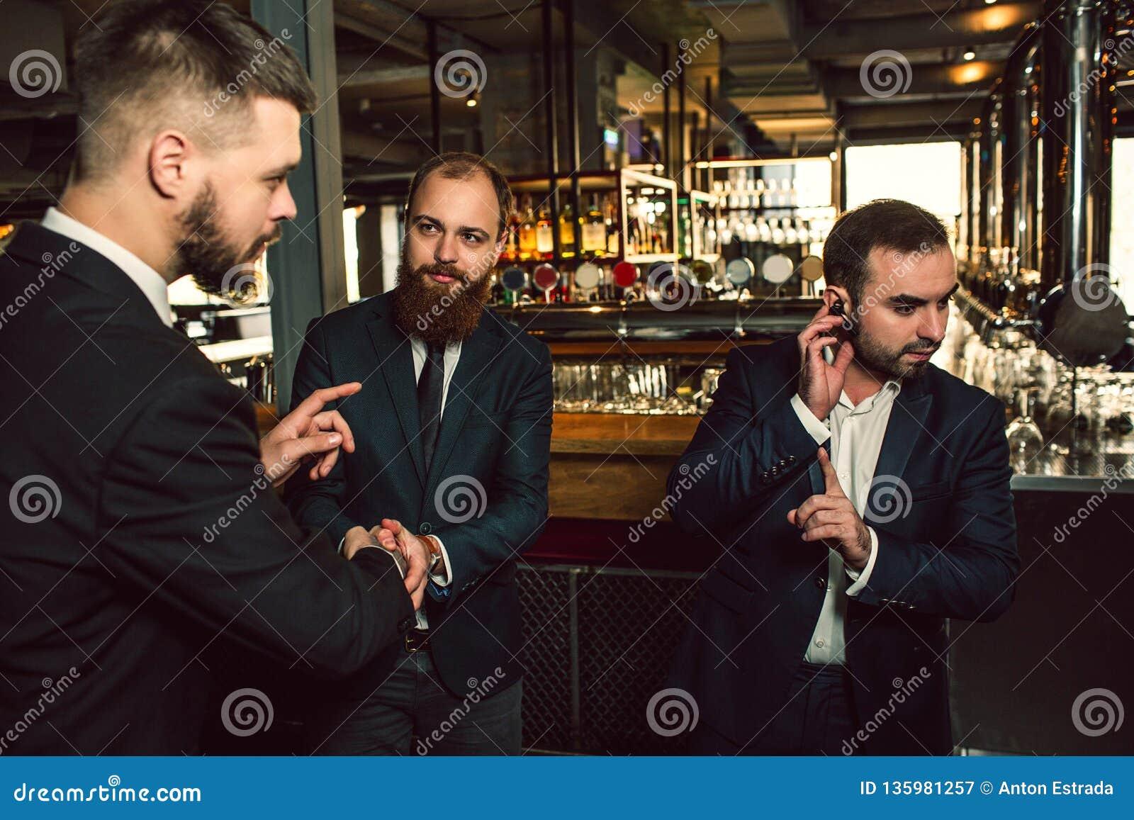 Tre unga män står i bar En hållhand på headphonen Han visar upp fingret Andra blick för ung man först och att försöka till